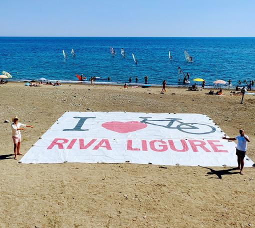 A Riva Ligure, uno striscione sulla spiaggia per salutare il passaggio della Milano-Sanremo